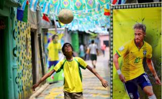 An Indian boy dribbles a ball next to a poster of Brazilian footballer Neymar in a lane decorated with Brazilian flags in Kolkata on 2 July 2018.