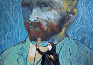 in_pictures A woman takes a selfie with a large mural of Van Gogh