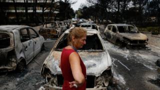 Veículos completamente destruídos pelo fogo na Grécia - em primeiro plano, uma mulher de blusa vermelha chora