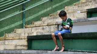 「シャペコエンセ」のスタジアムで選手たちの死を悲しむ少年。競技場外にはほかにも大勢のサポーターが集まった。