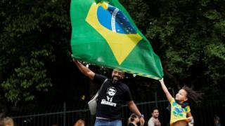 Supporters of Jair Bolsonaro wave a Brazilian flag