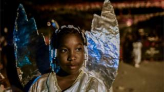"""An Afro-Colombian girl in an angel costume takes part in the """"Adoraciones al Nino Dios"""" celebrations in Quinamayo, department of Valle del Cauca, Colombia, on February 18, 2018."""