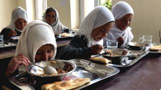 دختران با یونیفرم خاکستری، چادرهای سفید در صفهای طولانی از صنف بیرون میشوند، دستهایشان را میشورند و بعد از دریافت غذا دوباره به کلاس بر میگردند