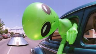 Un extraterrestre verde inflable en un auto.