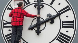 bir adam büyük bir saati ayarlarken