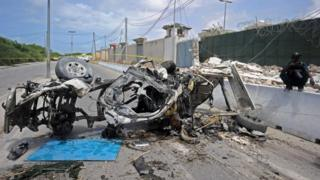 "Somali soldiers stands on guard next to the wreckage of a car bomb outside the UN""s office in Mogadishu on July 26, 2016."
