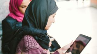 Women wearing headscarves look at a tablet computer