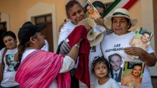 A family holds signs of a missing loved one during a march in el Fuerte, Sinaloa