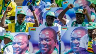 Zanu-PF supporters in Zimbabwe hold up pictures of President Emmerson Mnangagwa at a rally on 28 July 2018