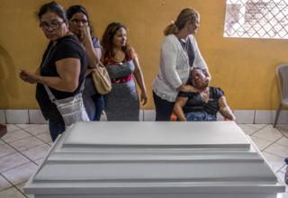Friends and family of five-month-old Matías Pavón mourn next to his coffin in Managua in June 2018