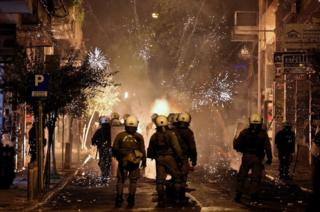 Fireworks explode next to riot police