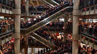 """Poppies fall through the atrium of the Lloyd""""s building during the Lloyd""""s of London Armistice commemoration service."""