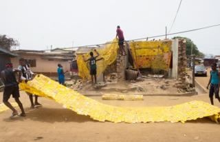 People spreading out yellow tapestry created by artist Serge Attukwei Clottey on a road in La - Accra, Ghana