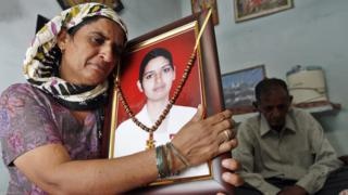 Preeti Rathi's parents with a photograph of their daughter
