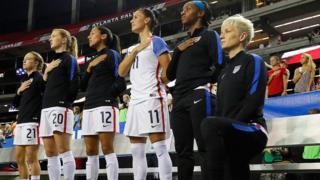 Megan Rapinoe kneels during the US national anthem