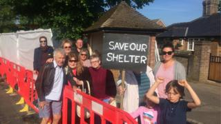 Residents of Caddington protest against the planned demolition of their village bus stop.