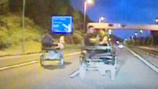 Two men racing their horse and traps on the M4