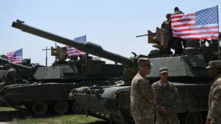 "US soldiers stand by Abrams Battle Tanks bearing the US flag prior to the opening ceremony of the joint multinational military exercise ""Noble Partner 2017"""