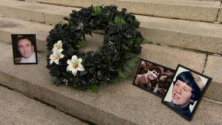 The families laid a wreath adorned with three lilies, one for each of the victims who are yet to be found