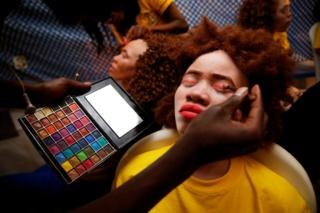 A make up artist works on a participant
