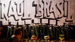 """Flores e homenagens em frente a muro grafitado: """"Raul Brasil"""""""