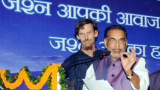 कार्यक्रम के दौरान केंद्रीय कृषि मंत्री राधा मोहन सिंह के पीछे खड़े हैं ज्यां द्रेज