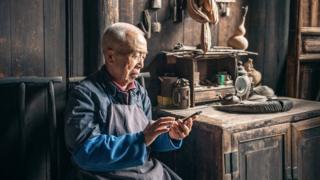 中国老人在木屋前用手机