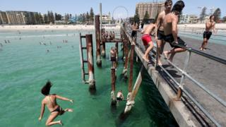 Teenagers jump off the jetty at Glenelg beach in Adelaide during a heatwave