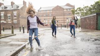Meninas pulam e sorriem na rua sob chuva