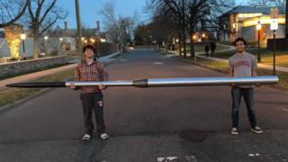 Students Joshua and Saad Mirza hold the space rocket they designed and built