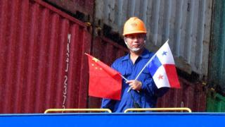 """Crew members of Chinese Cosco Shipping Rose container ship stand on deck, upon arrival at the newly inaugurated Cocoli locks during the visit of China""""s President Xi Jinping, in the Panama Canal, on December 3, 2018, - Chinese President Xi Jinping is on an official visit to Panama after attending the G20 Summit in Argentina. (Photo by Luis Acosta / AFP)LUIS ACOSTA/AFP/Getty Images"""