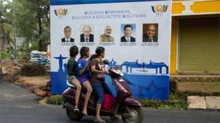 Locals in Goa stare at a poster for the Brics meeting