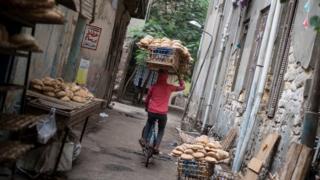 سائق دراجة هوائية يحمل فوق رأسه رفا خشبيا مليئا بقطع الخبز (العيش باللهجة المصرية) ويوزعها في القاهرة.