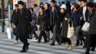 Businessmen and women cross the road in Tokyo