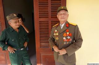 Pham Xuan Do (right), 77, buttoning his original uniform in the presence of retired captain Le Quang Kieu (left), 68, and retired lieutenant sergeant Hoang Ding Li (center), 73, at Friendship Village