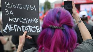 A woman with her back to camera holds a sign, with text in Russian.