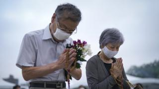 An elderly couple prays for victims in front of a cenotaph in Hiroshima Peace Memorial Park