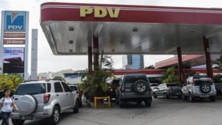 Imagem mostra carras em fila para serem abastecidos em posto de combustíveis com a bandeira da estatal venezuelana PDV