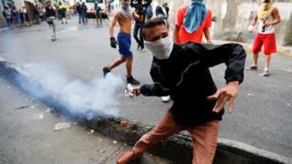 Một người biểu tình ném bình xịt hơi cay khi xô xát với Lực lượng Vệ binh Quốc gia trong một cuộc biểu tình gần Thủ đô Caracas.