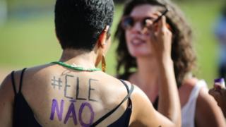 Mulher pinta outra em manifestação contra candidato presidencial Bolsonaro