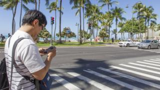 A man looks at his mobile phone before crossing the street in Honolulu