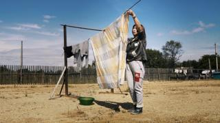 in_pictures A Chinese woman hangs out the washing on a farm at Dimitrovo