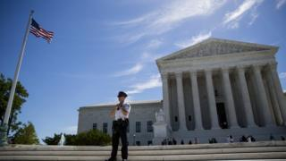 A police officer is seen outside the US Supreme Court after it was announced that the court will allow a limited version of President Donald Trump's travel ban to take effect June 26, 2017 in Washington, DC. T