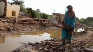 A Sudanese woman walks amid the rubble of houses destroyed following heaving floods, in Geli, some 40 km north of Khartoum, Sudan, 25 August 2019