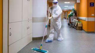 عامل نظافة مزود بمعدات الوقاية الشخصية الكاملة في المستشفى