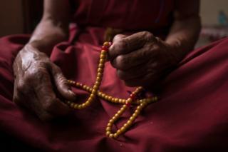 An elderly nun holds prayer beads