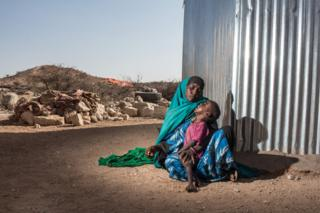 Hodan, a mother of five, holds her two year old son Harun in the town of Kiridh, Somaliland.