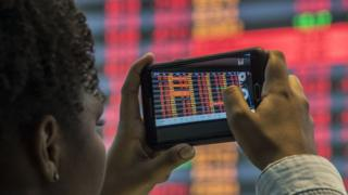 A visitor take pictures of a board at the Sao Paulo Stock Exchange (B3), in Sao Paulo, Brazil, on May 18, 2017. Brazilian financial markets plummeted on opening Thursday in the wake of a bombshell report that President Michel Temer approved paying hush money to a corrupt politician. T
