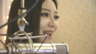 Lele Tao sings in front of a microphone.