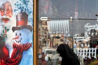 An Egyptian woman wearing a full veil walks in front of a Christmas decorated shop in Cairo, Egypt - Monday 3 December 2018